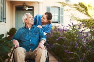 caregiver assisting an elder man in a wheelchair