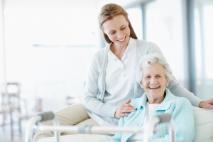 caregiver sitting and laughing with a happy senior
