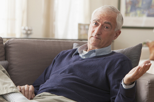 man sitting on sofa with hand extended. expressing dementia denial