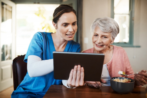 caregiver and senior woman at breakfast looking at tablet