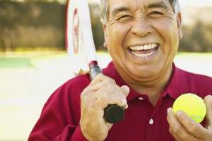 happy senior man exercising playing tennis