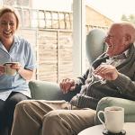 happy caregiver providing respite care services to senior