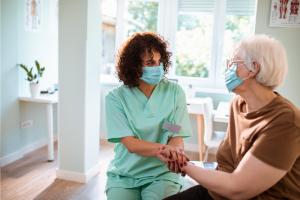 masked-caregiver-comforting-senior-woman