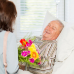 Senior man receives flowers in bed