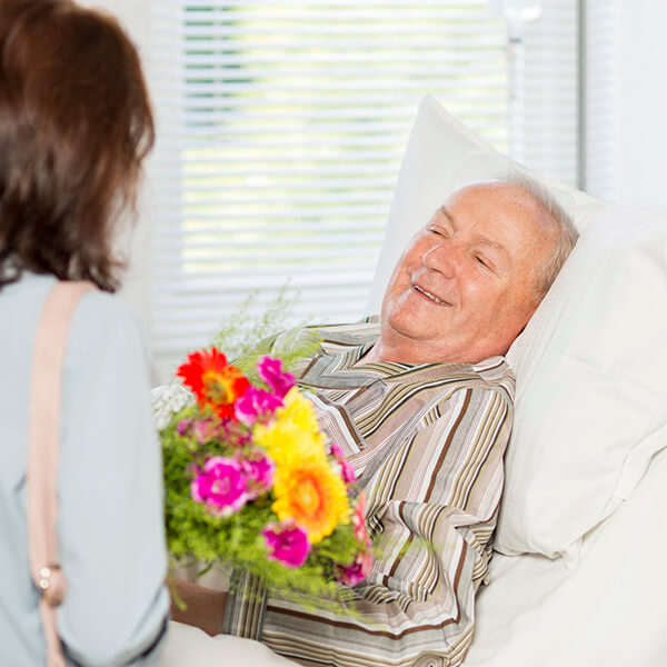 Senior man receives flowers in bed
