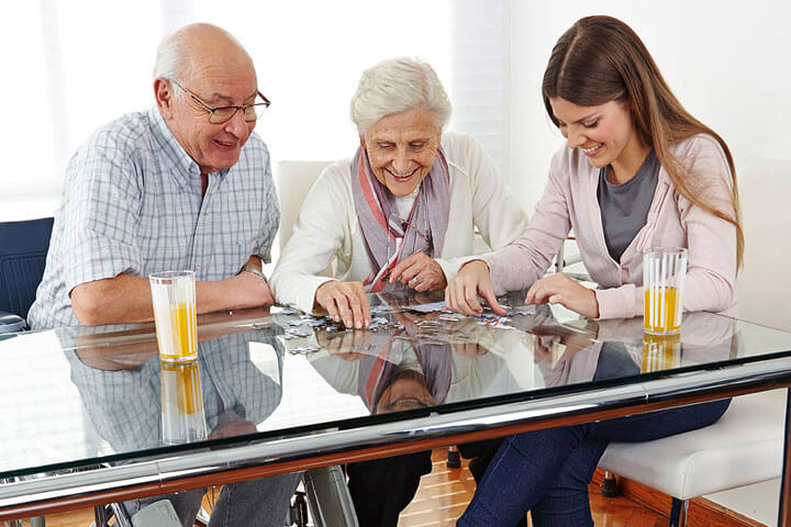 Caregiver with a senior couple working on a puzzle together
