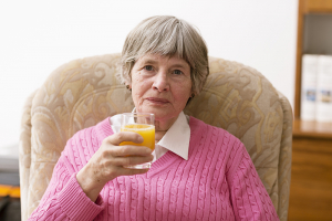 senior woman drinking orange juice in a seat at home